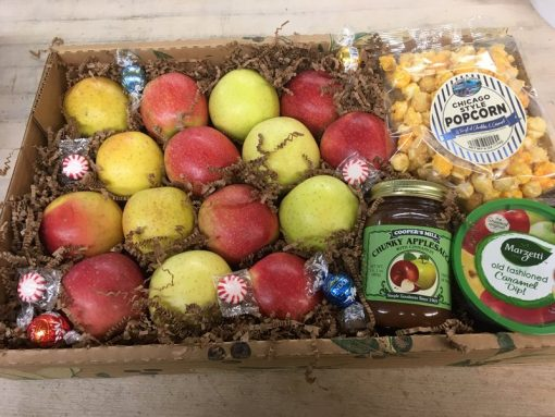 The snack box contains apples, popcorn, caramel dip and applesauce