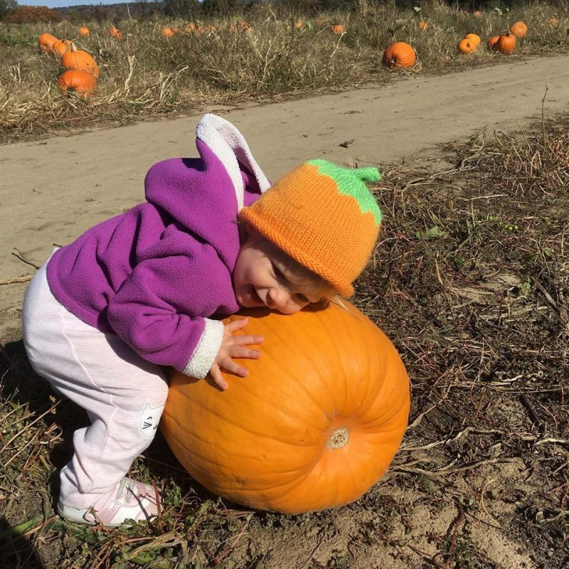 Abbie hugging the pumpkins out in the patch